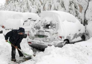 person shoveling snow off car