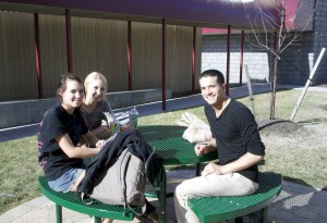 students sitting at table outside