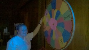 A D'Youville Student Playing the Wheel of Fortune Game at the Black Light Party