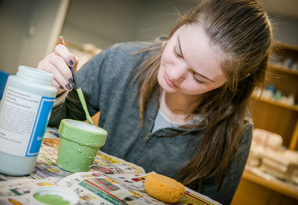 D'Youville student painting pottery