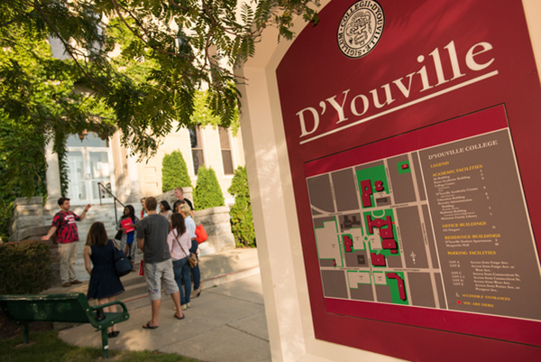 A group listens to an admissions ambassador on a campus tour of D'Youville College